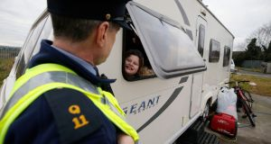 A garda is greeted by a child at a halting site on the Balgaddy Road in  Clondalkin, Dublin on Friday. Photograph Nick Bradshaw/The Irish Times.
