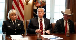 "Donald Trump, with Carolyn ""Bunny"" Welsh, sheriff of Chester County, Pennsylvania (L) and AJ Louderback, sheriff of Jackson County, Texas, attends a roundtable discussion on border security in the cabinet room of the White House on Friday. Photograph: Jacquelyn Martin/AP"