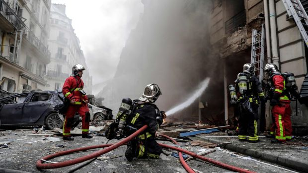 Firefighters extinguish a fire after the explosion of a bakery on the corner of the streets Saint-Cecile and Rue de Trevise. Photograph: Thomas Samson/AFP/Getty Images