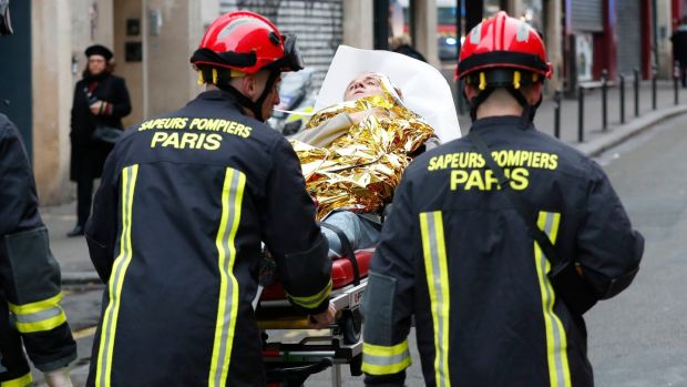 Firefighters evacuate a wounded man on a stretcher from the scene of a gas leak explosion in Paris. Photograph: Thibault Camus/PA
