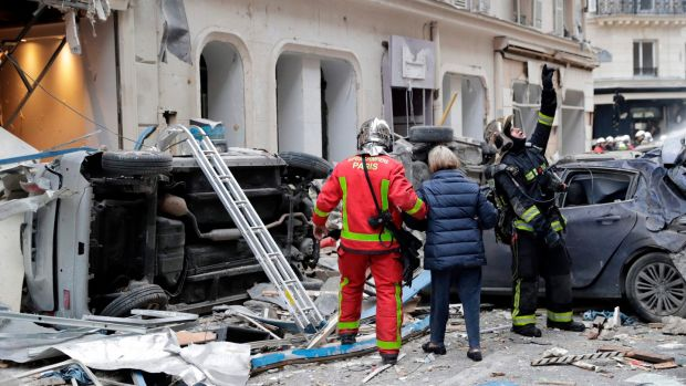 A woman is evacuated by firefighters after the explosion of a bakery on the corner of the streets Saint-Cecile and Rue de Trevise in central Paris. Photograph: Thomas Samson/AFP/Getty Images