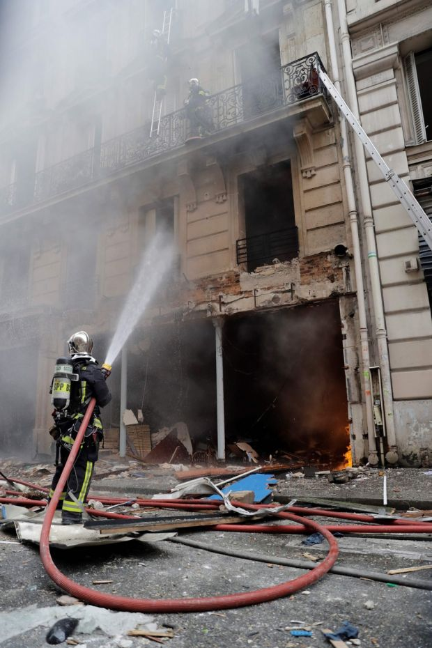 Firefighters extinguish a fire after the explosion of a bakery on the corner of the streets Saint-Cecile and Rue de Trevise in central Paris. Photograph: Thomas Samson/AFP/Getty Images