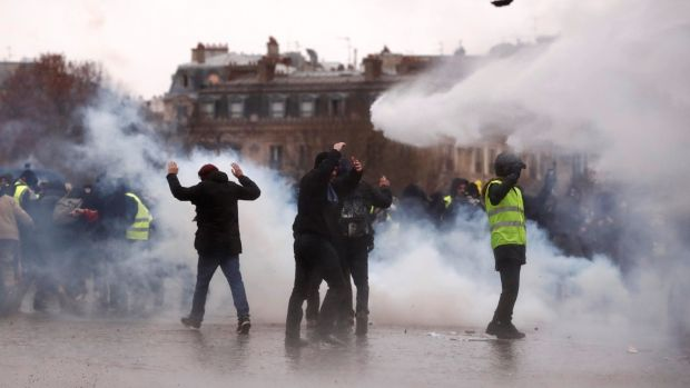 Protesters amid the tear gas near the Arc de Triomphe. Photograph: Reuters