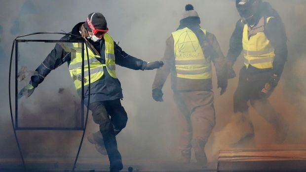A protester in Nimes attempts to kick a tear gas canister towards police. Photograph: EPA