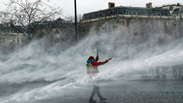 Water canon is directed at a yellow vest protester at the Arc de Triomphe in Paris. Photograph: EPA