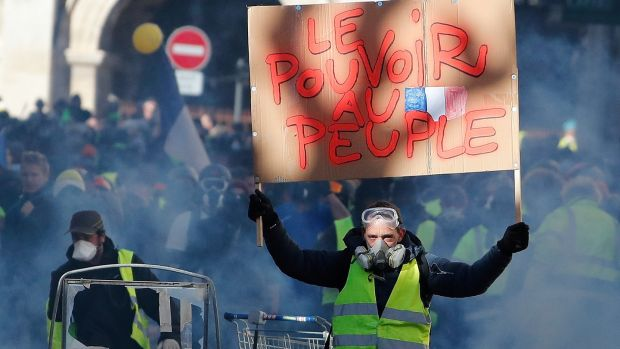 "The yellow vests clashed with police in Nimes. The banner reads ""The power for the people"". Photograph: EPA"
