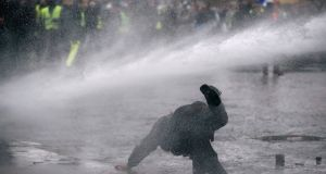 Police use a water cannon during a demonstration by the yellow vests movement near the Arc de Triomphe in Paris. Photograph: Reuters
