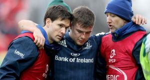 Leinster's Luke McGrath  is helped from pitch. Photograph: Dan Sheridan/Inpho
