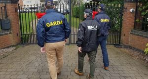 Gardaí and an officer from the National Crime Agency in the UK at a property in the Tamworth area on Saturday. Photograph: National Crime Agency