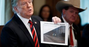 "US president Donald Trump presents a ""typical standard wall design"" as he participates in a discussion on border security and safe communities. Photograph:  Shawn Hew/EPA"