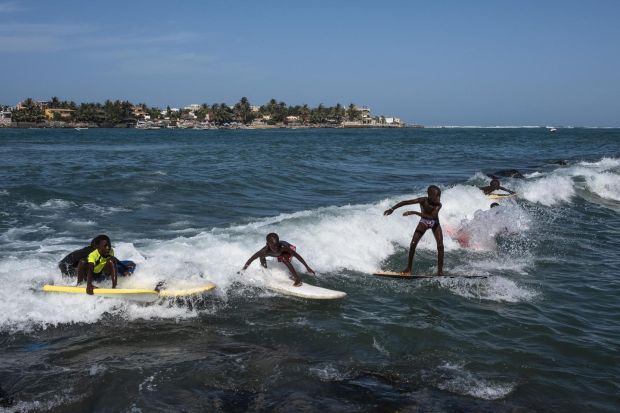 Boys surfing along Ngor beach in Dakar, Senegal. This seaside city on the western coast of Africa is a haven of peace in a region known for unrest. Photograph: Daniel Rodrigues/The New York Times