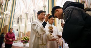 Chinese worshippers receive the Eucharist from a priest as they attend a Mass on  Christmas Eve 2018 at a Catholic church in Beijing. Photograph:  Wang Zhao/AFP/Getty Images
