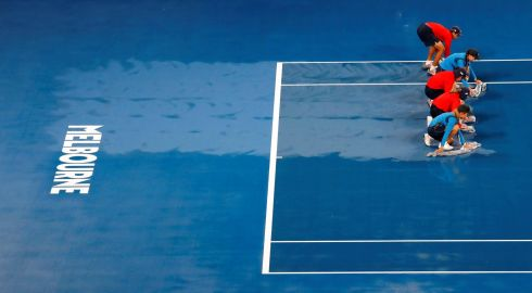 At the Australian Open in Melbourne staff wipe rainwater from the court. Photograph: Kim Kyung-Hoon