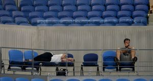 A spectator sleeps at Margaret Court Arena as s Garbine Muguruza and  Johanna Konta played their  second round match until after 3am at the Australian Open tennis championships in Melbourne. Photograph: Mark Baker/AP
