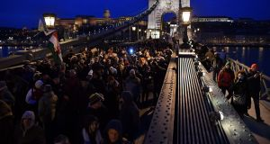 "Demonstrators march on the Chain Bridge during a protest against the recent amendments to the labour code, dubbed ""slave law"" by opposition forces, in Budapest, Hungary, on Saturday.  Photograph: Marton Monus/EPA"