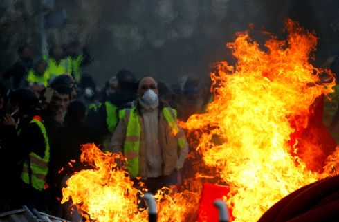 "BURNING RAGE: Protesters behind a fire as they attend a demonstration of the ""yellow vests"" movement in Angers, France. Photograph: Stephane Mahe/Reuters"
