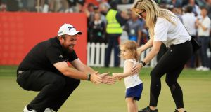 Shane Lowry celebrates with wife Wendy Honner and daughter Iris Lowry on the 18th green after winning the Abu Dhabi HSBC Golf Championship. Photo: Andrew Redington/Getty Images