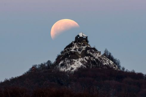 The moon fully shadowed by the Earth is seen above the castle of Salgo during a total lunar eclipse near Salgotarjan, some 109km northeast of Budapest, Hungary. Photograph:  Peter Komka Hungary