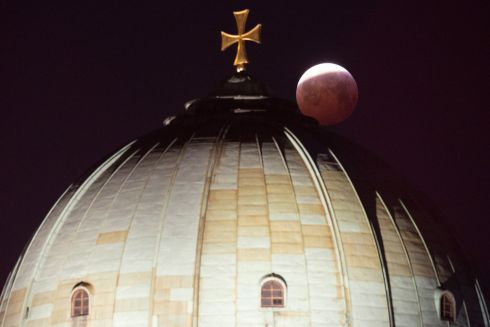 A view of the lunar eclipse over the cross on top of the Elizabeth Church in Nuremberg, Germany. Photograph: Timm Schamberger/EPA