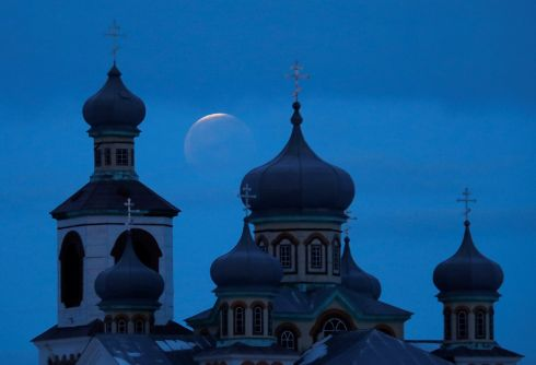 "The ""super blood wolf moon"" is seen behind an Orthodox church during a lunar eclipse in the village of Turets, Belarus. Photograph: Vasily Fedosenko/Reuters"