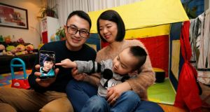 Ray Chen and his wife, Ting Ting, with their son Cooper (3) and a  photograph of their daughter Coleen (7). Coleen is being raised in China by Ray's parents while they wait to secure her a visa. Cooper is being raised by his parents in Dublin Photograph Nick Bradshaw/The Irish Times