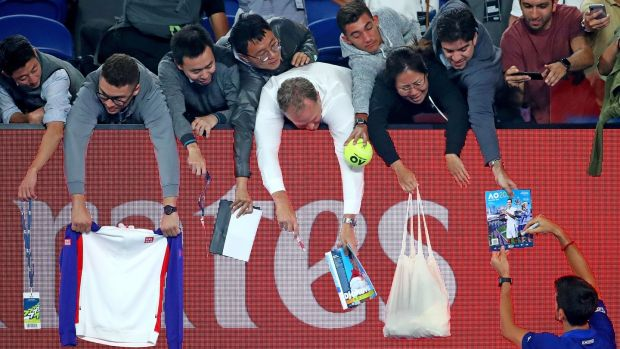 Novak Djokovic signs autographs after his fourth round win over Daniil Medvedev. Photograph: Scott Barbour/Getty Images