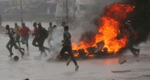 People run at a protest as barricades burn  in Harare,  Zimbabwe last week. Photograph: Philimon Bulawayo/Reuters