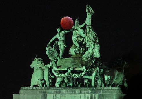 The moon is seen beside a quadriga on the top of the Cinquantenaire Arch during a total lunar eclipse, known as the Super Blood Wolf Moon, in Brussels, Belgium. Photograph: Yves Herman/Reuters