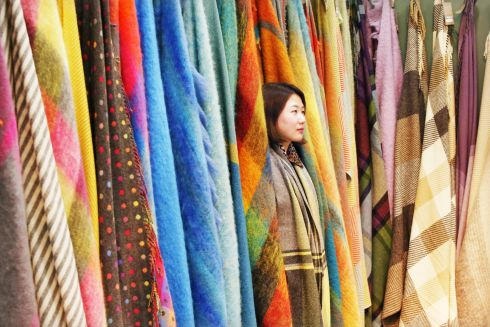 Jaesin Yu from Foxford Woollen Mills stands among some colourful throws as she waits for customers on the second day of Showcase 2019 in the RDS.  Photograph: Leon Farrell/Photocall Ireland