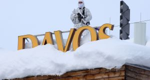 An armed member of the Swiss police watches from the snow-covered roof of the Hotel Davos ahead of the World Economic Forum in Davos, Switzerland  on Monday. World leaders, influential executives, bankers and policy makers are attending the 49th annual WEF meeting, which runs until January 25th.  Photographer: Simon Dawson/Bloomberg
