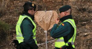 Two officers from Spain's Guardia Civilstand next to a heart-shaped banner where two-year-old Julen fell into a deep well. Photograph: Reuters/Jon Nazca