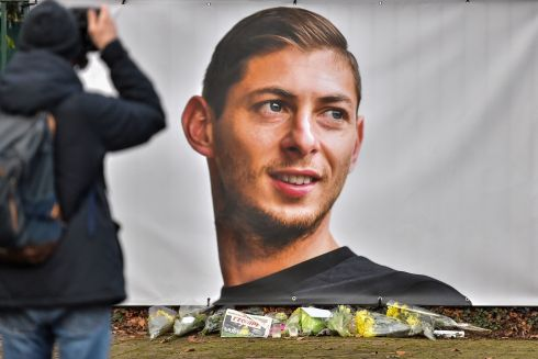 MISSING: A man takes a picture of flowers displayed next to a portrait of Emiliano Sala in front of the entrance of the FC Nantes football club training center, La Joneliere, in La Chapelle-sur-Erdre on January 23rd, two days after the plane of Argentinian forward vanished during a flight from Nantes in western France to Cardiff in Wales. The 28-year-old striker is one of two people still missing after contact was lost with the light aircraft he was travelling in on January 21st. Sala was on his way to the Welsh capital to train with his new teammates for the first time after completing a £15 million move to Cardiff City. Photograpgh: Loic Venance/AFP/Getty