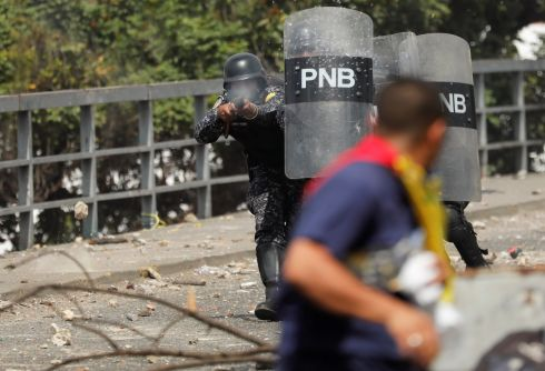SHIELDS UP: A National Police officer fires rubber bullets during a protest against Venezuelan president Nicolas Maduro's government in Caracas, Venezuela on January 23rd. Photograph: Manaure Quintero/Reuters