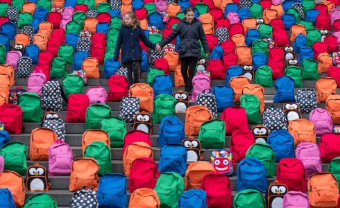 SCHOOL BAGS: Joana (left) and Jessica Ferreira stand among an installation of 800 school bags created by the charity WaterAid on the steps of St Paul's Cathedral, London, representing the 800 children who die every day due to dirty water. Photograph: Dominic Lipinski/PA Wire