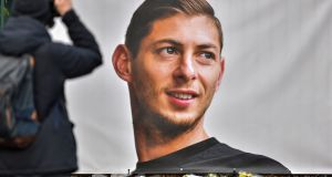 A man takes a picture of flowers displayed next to a portrait of Emiliano Sala in front of the entrance of the FC Nantes football club training centre. Photograph:  Loic Venance/AFP