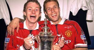 Ole Gunnar Solskjaer and Ronny Johnson of Manchester United celebrate in the dressing room with the FA Cup after the 1999 final win over Newcastle. Photo: John Peters/Manchester United via Getty Images