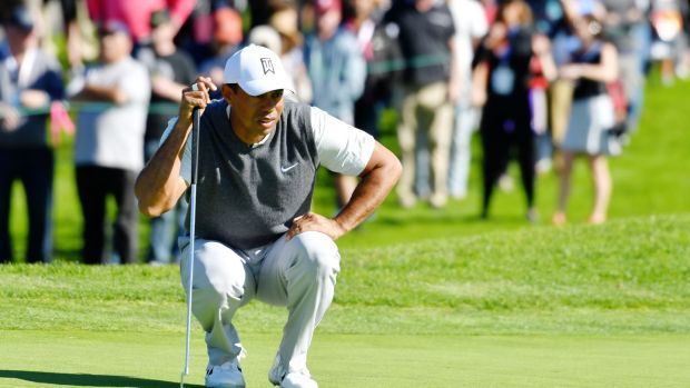 Woods prepares to putt on the first green. Photo: Donald Miralle/Getty Images
