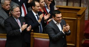 Greece's prime minister Alexis Tsipras (right), accompanied by Greek alternate minister of foreign affairs George Katrougalos (left) and other members of his government applaud following a vote that ratified the Prespa Agreement at the parliament in Athens. Photograph: Michael Varaklas/AP
