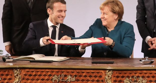 French president Emmanuel Macron and German chancellor Angela Merkel exchange the French-German friendship treaty during the signing ceremony  in Aachen, Germany, on Tuesday. Photograph: Ludovic Marin/AFP/Getty Images