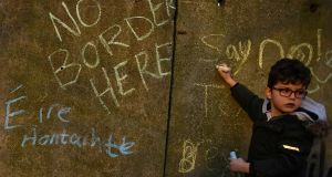 A boys writes a message on a mock border wall during a protest by anti-Brexit campaigners, Borders Against Brexit in Carrickcarnan, Co Louth on Saturday. Photograph: Clodagh Kilcoyne/Reuters
