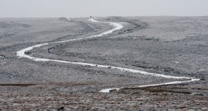 A couple walk on the horizon on a  winding  road near the Sally Gap, Co Wicklow last week amid the first light snow falls of the year. Photograph: Alan Betson
