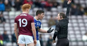 Referee Derek O'Mahoney shows a black card to Galway's Peter Cooke and Killian Brady of Cavan during the Allianz Football League Division 1 match at  Pearse Stadium, Galway on Sunday. Photograph: Tommy Grealy/Inpho
