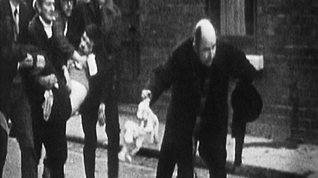 Powerful image: Bishop Daly was filmed waving a white handkerchief on Bloody Sunday, as attempts are made to carry Jackie Duddy to safety. Photograph: RTÉ Archives