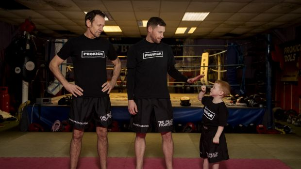 Billy Murray with amateur world k1 kickboxing champion Johnny Smith and Leo Smith (4) who is Billy's grandson, and Johnny's son at Prokick Gym in Belfast. Photograph: Liam McBurney