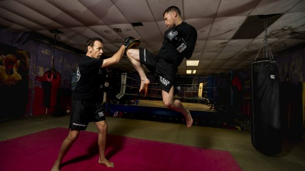 Billy Murray holds the pads as amateur world kick-boxing champion Johnny Smith strikes a flying knee during a sparring session at Prokick Gym in Belfast. Photograph: Liam McBurney