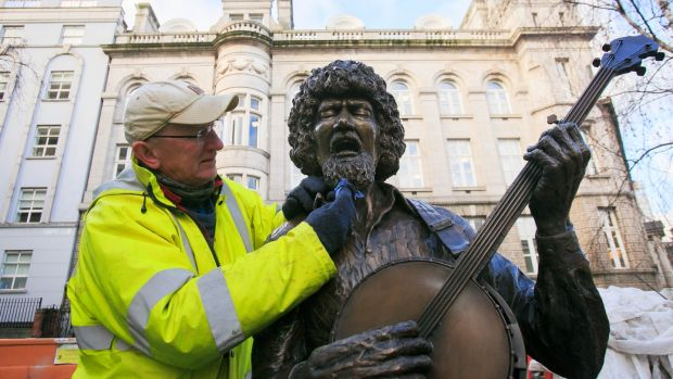 Sculptor John Coll who created the Luke Kelly Statue puts the finishing touches to the statue on South King Street, Dublin, to mark the 35th anniversary of the death of the musician. Photograph: Gareth Chaney/Collins