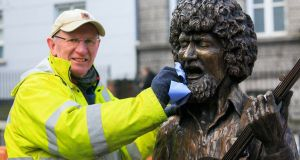 Sculptor John Coll  puts the finishing touches to his Luke Kelly statue on South King Street, to mark the 35th anniversary of the death of the musician. Photo: Gareth Chaney/Collins
