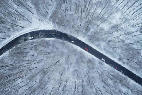 DRIVEN SNOW: An aerial view shows cars driving on a street in a snow-covered forest near Cologne, Germany. Photograph: Henning Kaiser/dpa/AFP/Getty Images