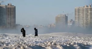 People walk along the lakefront  in Chicago, Illinois. Photograph: Scott Olson/Getty Images