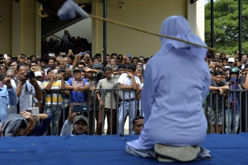CANING: An 18-year-old Indonesian woman is caned in public in Banda Aceh, Indonesia on January 31st, as punishment for being caught cuddling with her boyfriend in public - a crime under the conservative region's Islamic law. Photograph: Chaideer Mahyuddin/AFP